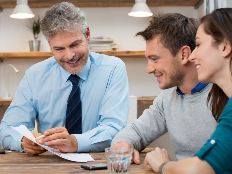 Young couple consulting financial agent for new future projects