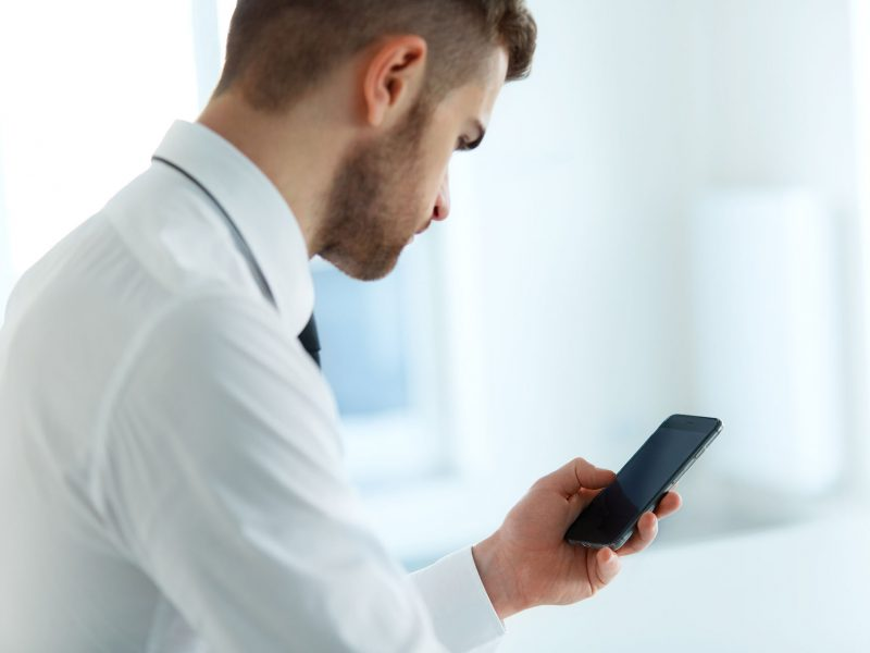 Business Man Reading Something on the Screen of His Cell Phone